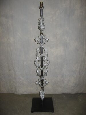 Gothic style custom iron floor lamp with a white, distressed finish and a dark iron base.