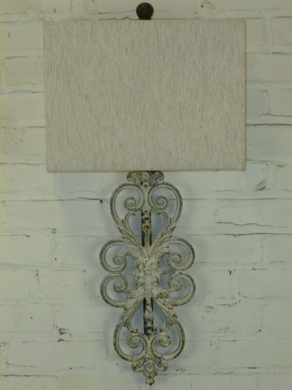 Scrollwork custom iron wall sconce with a white, distressed finish. Paired with a half rectangle linen lamp shade.
