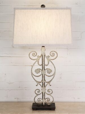 Flower scroll custom iron table lamp with a white, distressed finish and a dark iron base. Paired with a 16 inch rectangle linen lamp shade.