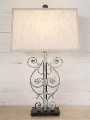 Small flower scroll custom iron table lamp with a white, distressed finish and a dark iron base. Paired with a 15 inch rectangle linen lamp shade.