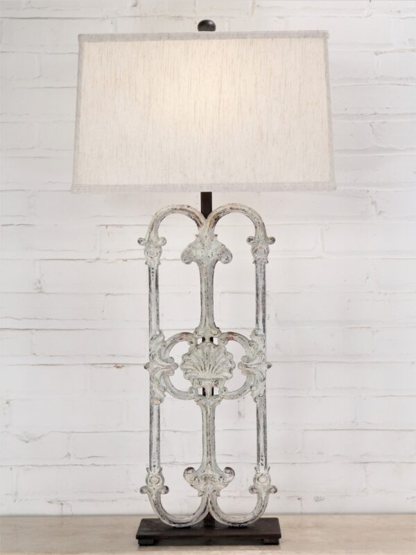 Shell custom iron table lamp with a white, distressed finish and a dark iron base. Paired with a 17 inch rectangle linen lamp shade.