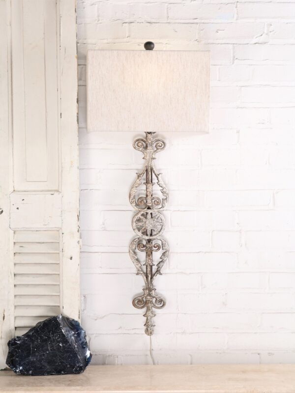 Spanish style custom iron wall sconce with a white, distressed finish. Paired with a half rectangle linen lamp shade