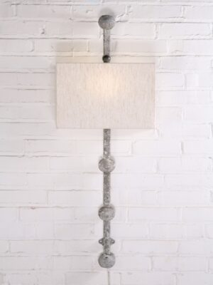 Custom iron wall sconce with a white, distressed finish and a half rectangle linen lamp shade.