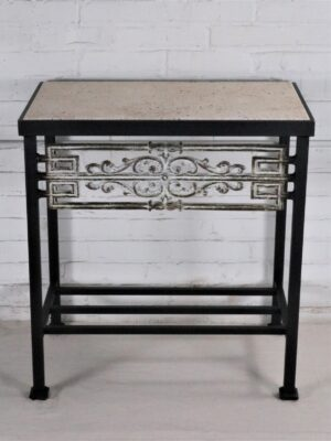 Ferro Designs LLC custom iron bedside table with a dark iron base finish, a white, distressed cast iron inset, and a travertine tile top